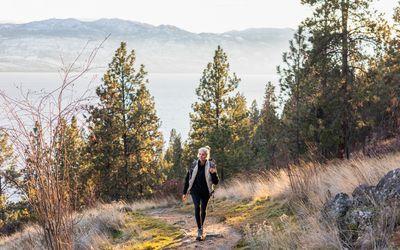 senior woman walking in woods on a coastal mountain trail