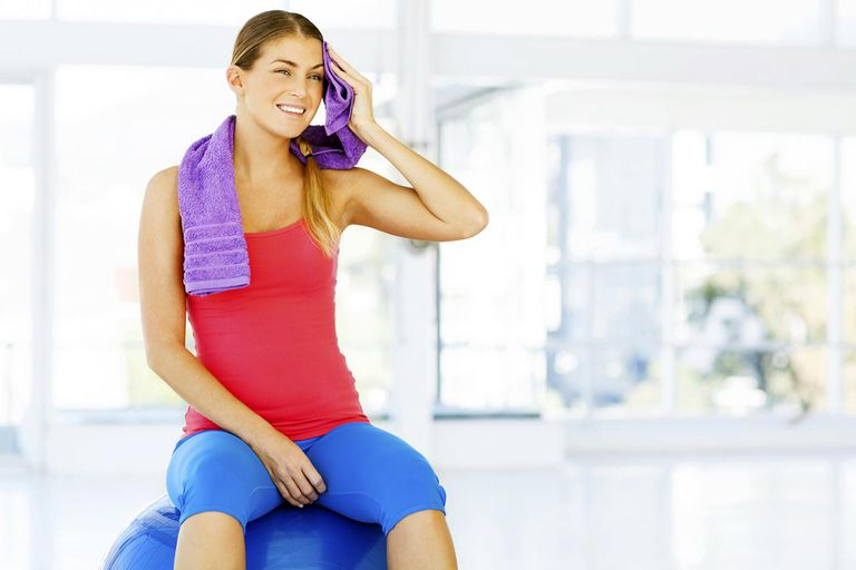 Beautiful young woman wiping face while sitting on fitness ball in gym. Horizontal shot.