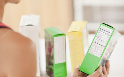 Woman checking nutrition label on box