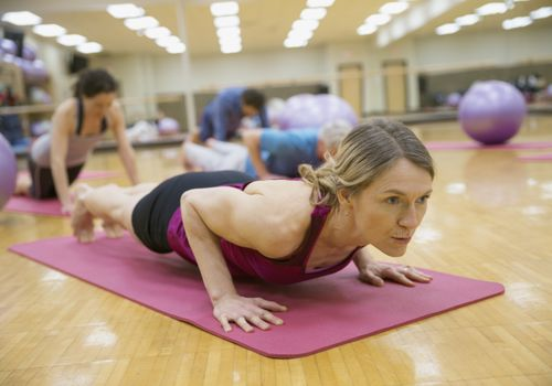 Woman in a low plank position on a yoga mat in an exercise studio
