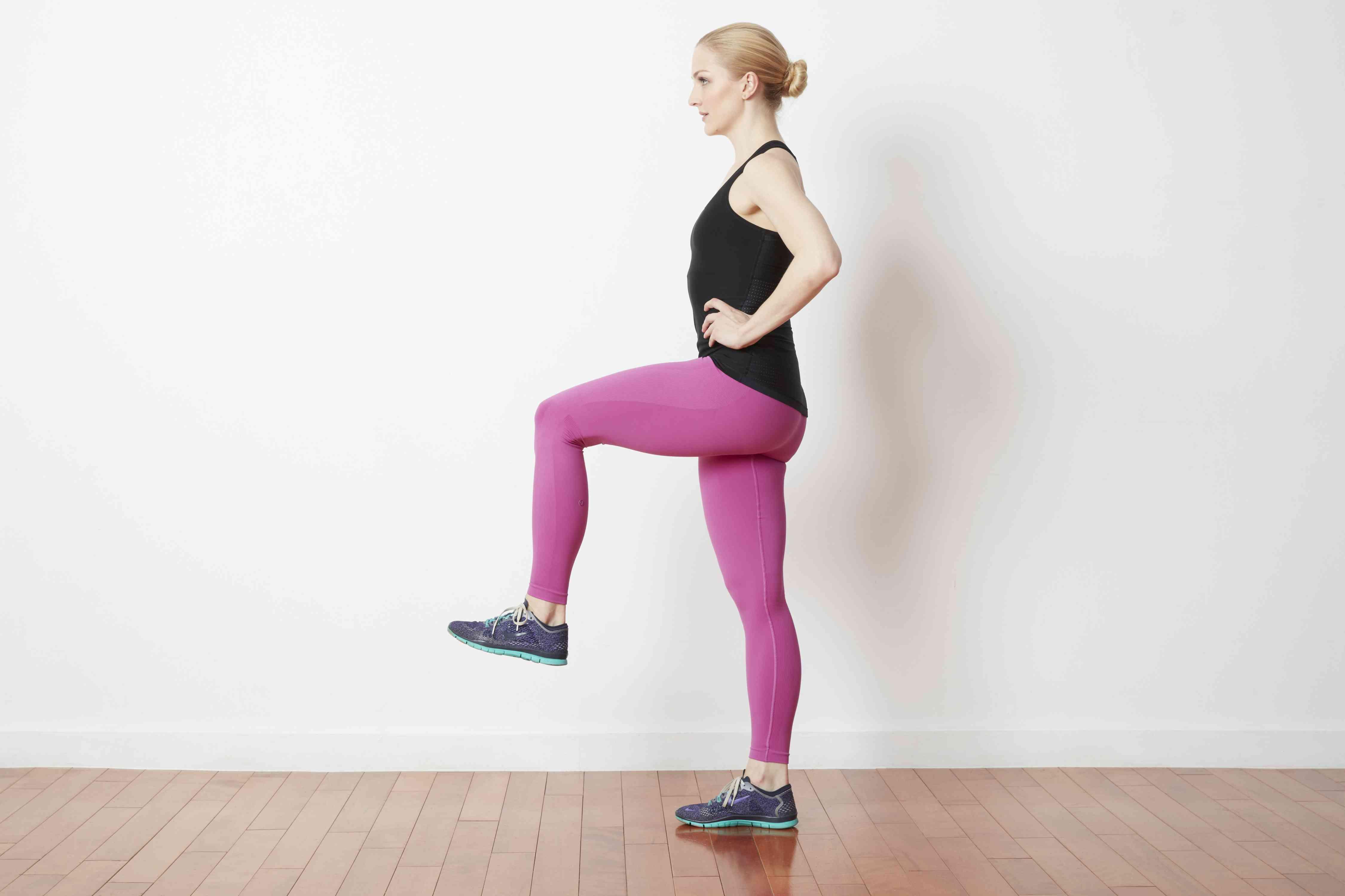 Woman balancing on one leg with knee raised