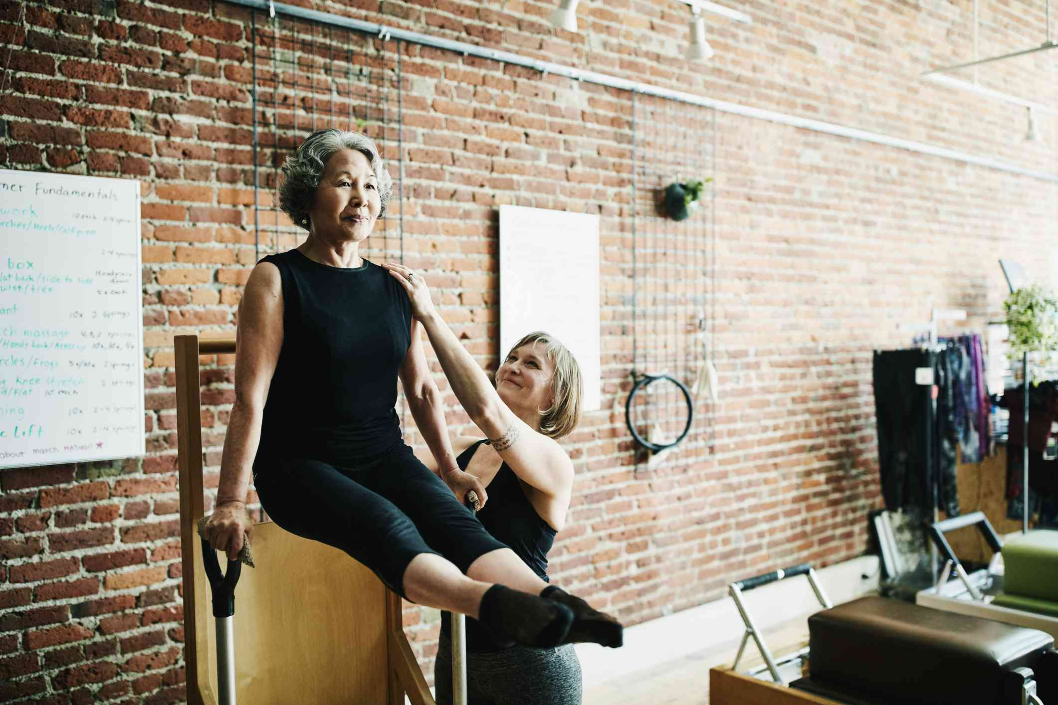 Female pilates instructor assisting mature student on high-low chair during class in exercise studio