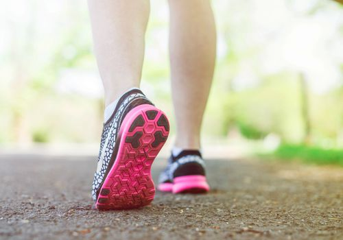 Vista baja de mujer caminando con zapatos para caminar