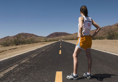 Runner with a number on her back standing on a paved road looking into the distance