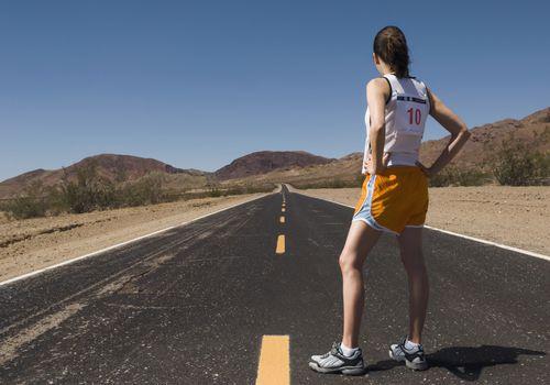 Corredor con un número en la espalda de pie en una carretera pavimentada mirando a lo lejos