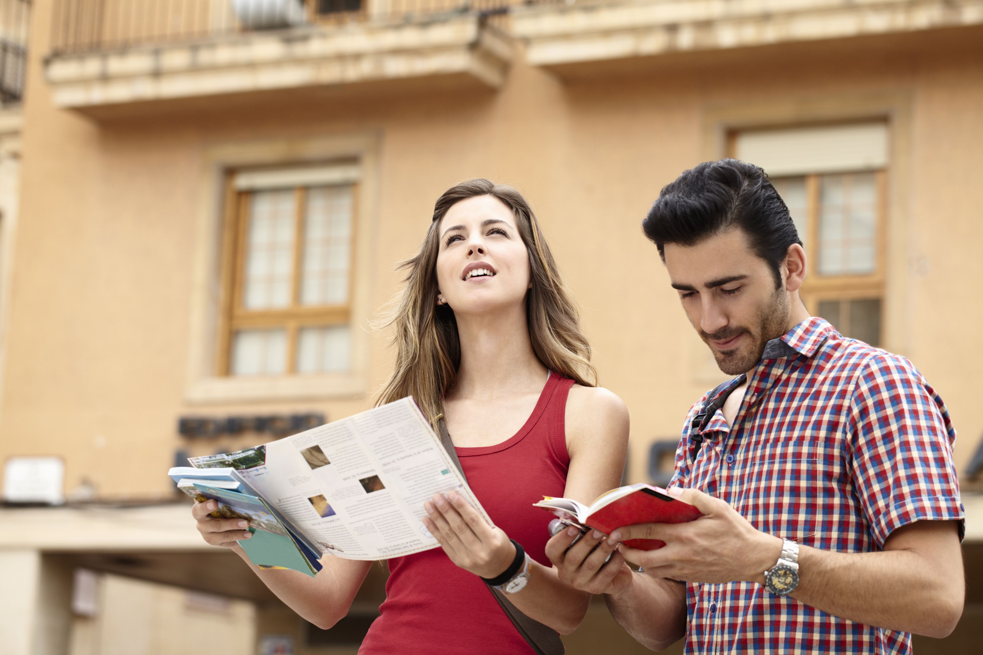 Hombre y mujer mirando un mapa y una guía turística