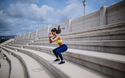 woman on stairs doing squat jumps