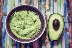 Bowl of guacamole and sliced avocado on colorful surface