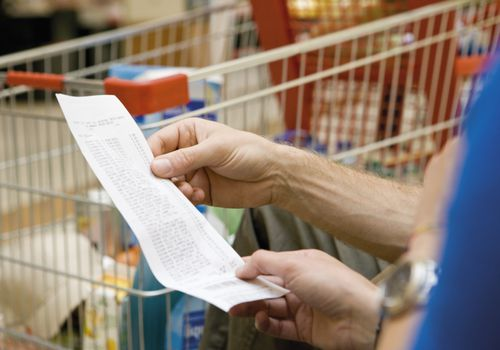 shopper looking at grocery receipt