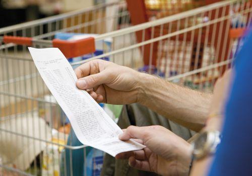 comprador mirando recibo de supermercado