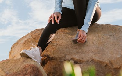 runner sitting on a rock with toe pain