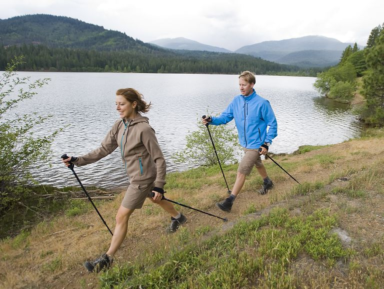 man and woman using walking poles to talk around lake