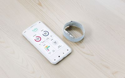 Amazon's new fitness wearable, Halo, and a phone screen opened to the Halo app.