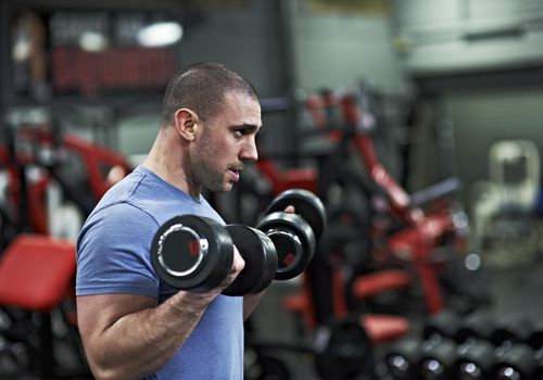 Athletic Male Lifting Dumbbells in Gym