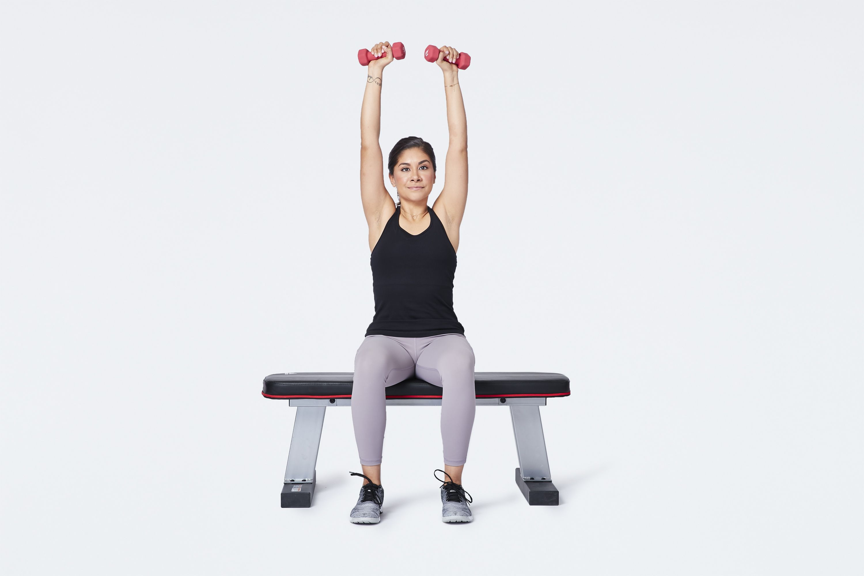 woman doing seated barbell shoulder press