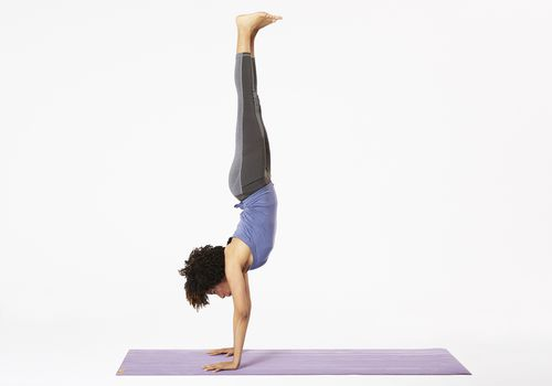 Woman on yoga mat doing handstand