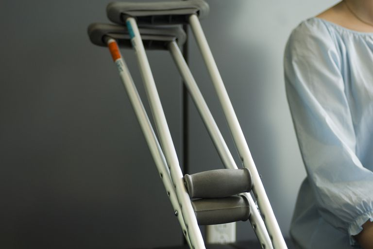 Pair of crutches resting beside seated patient