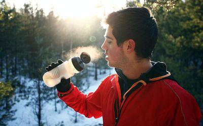 Runner drinking water in forest