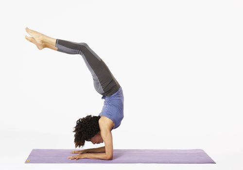 Mujer en estera de yoga haciendo pose de escorpión