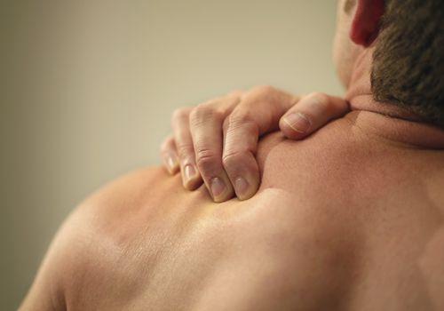 Hombre sujetando el hombro en dolor