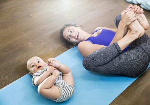 Mother and infant son in happy baby pose