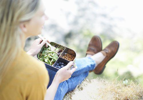 blonde woman eating vegan food outside