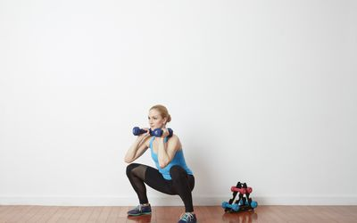 woman doing dumbbell shoulder squat