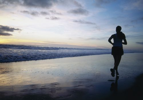 Woman Running on Beach in the Morning