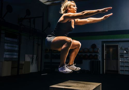 Woman jumping onto a box in the gym