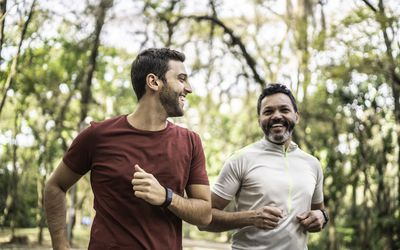 Male friends running together in a park