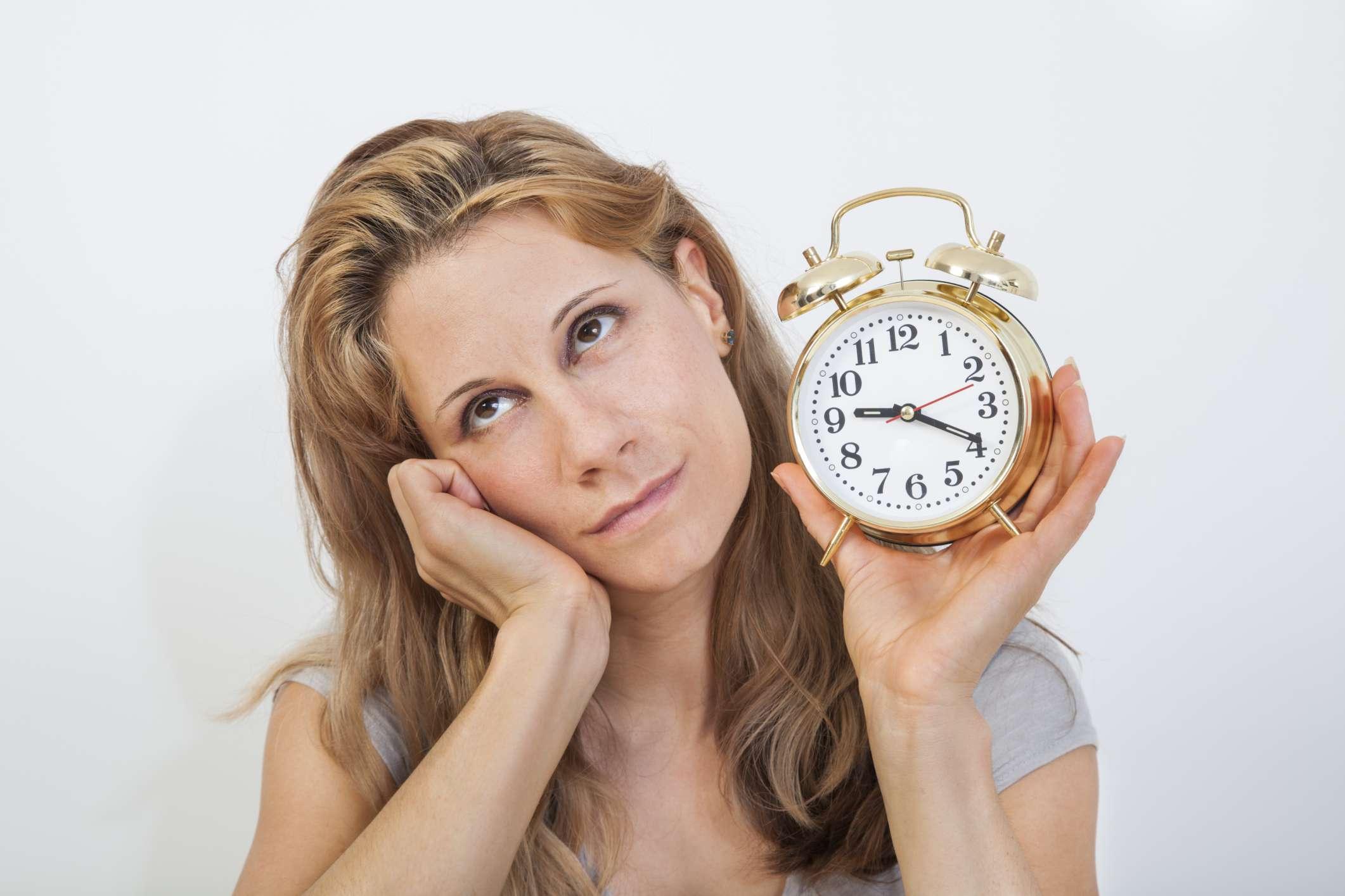 Imagen que muestra a una mujer sosteniendo un reloj con impaciencia