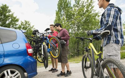 Men removing bicycles from bike rack on car