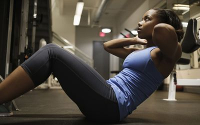 woman doing a sit-up on floor at gym