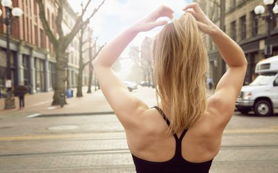 Rear view of young female runner stretching arms on street