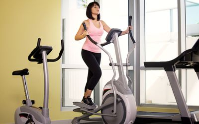 566435fa496 7 Benefits of Speed Walking. Woman exercising on cross trainer in gym