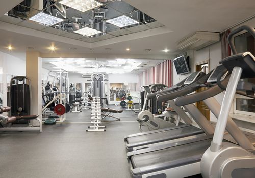 An empty gym with treadmills and other fitness equipment.