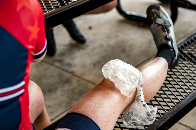 Bag of ice on an injured cyclist's knee