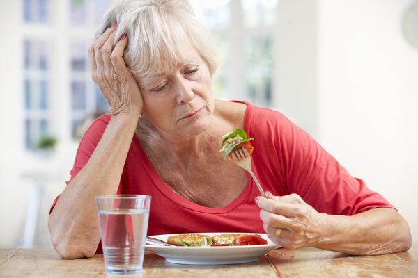 senior woman looking at salad on fork, not wanting to eat