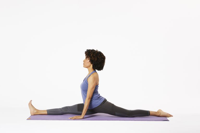 Woman on yoga mat in monkey pose