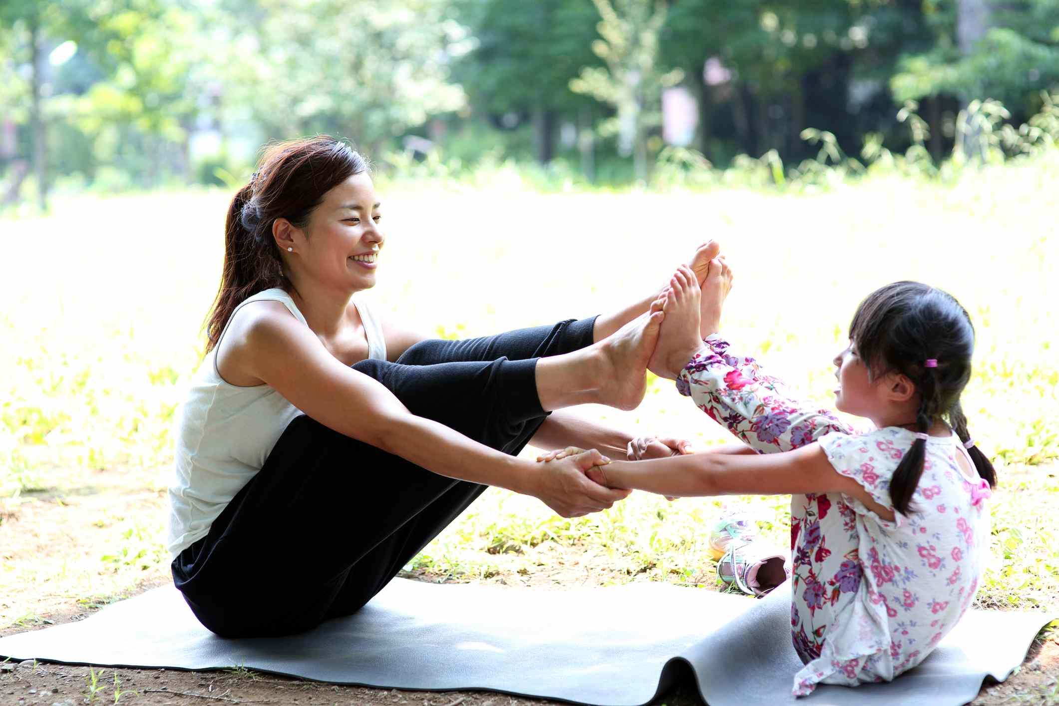 madre e hija haciendo yoga en el parque