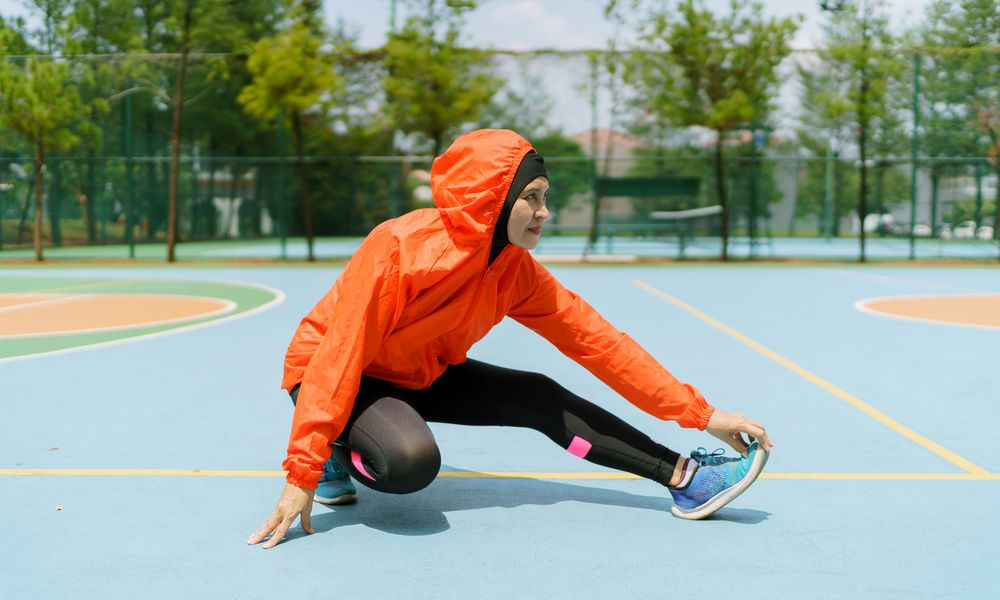 Muslim woman in running shoes and leggings stretching on a basketball court