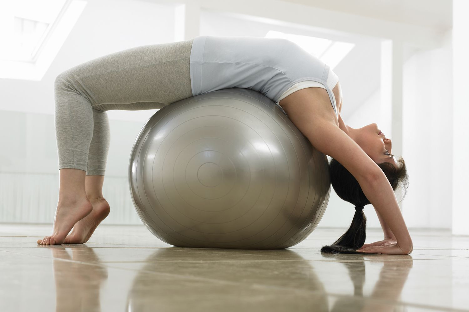 Woman doing a backbend over an exercise ball