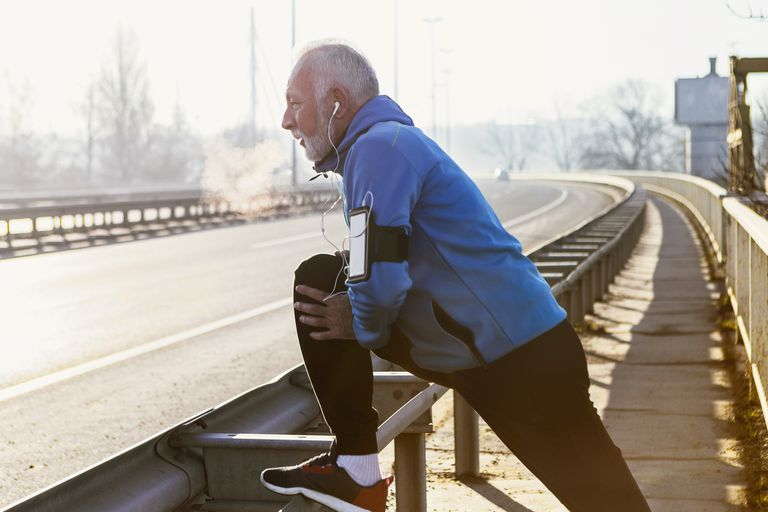 Senior man warming up for jogging on a city bridge