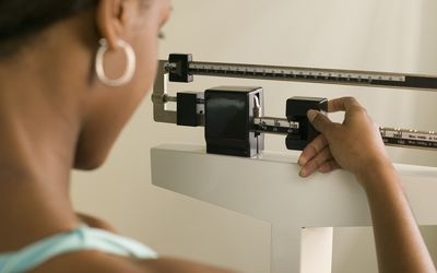 Woman on a scale weighing herself