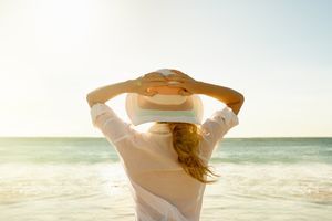 Woman in a hat and white shirt at the beach