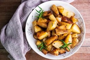 Oven-roasted potatoes with rosemary in a white bowl on a wooden surface