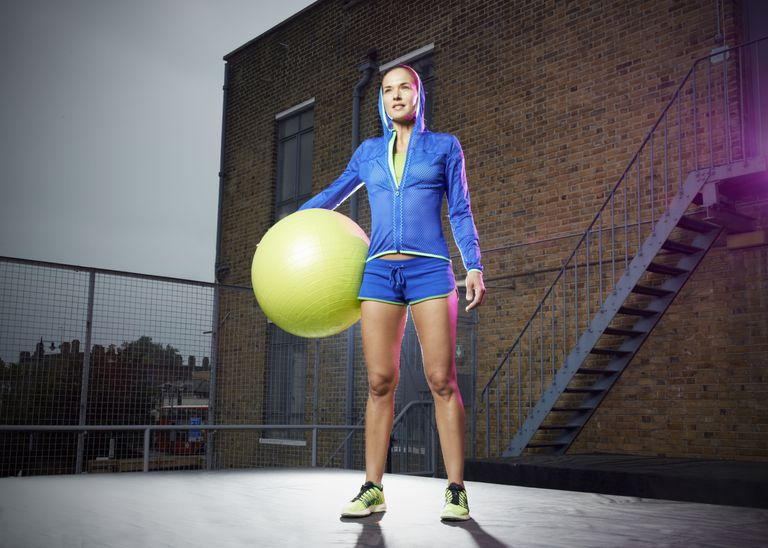Woman standing with exercise ball