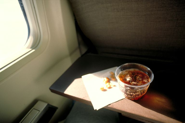 Soda and peanuts on aeroplane seat tray