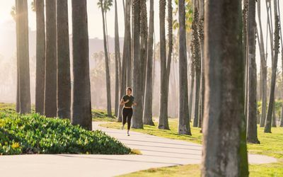 woman running through trees in a park