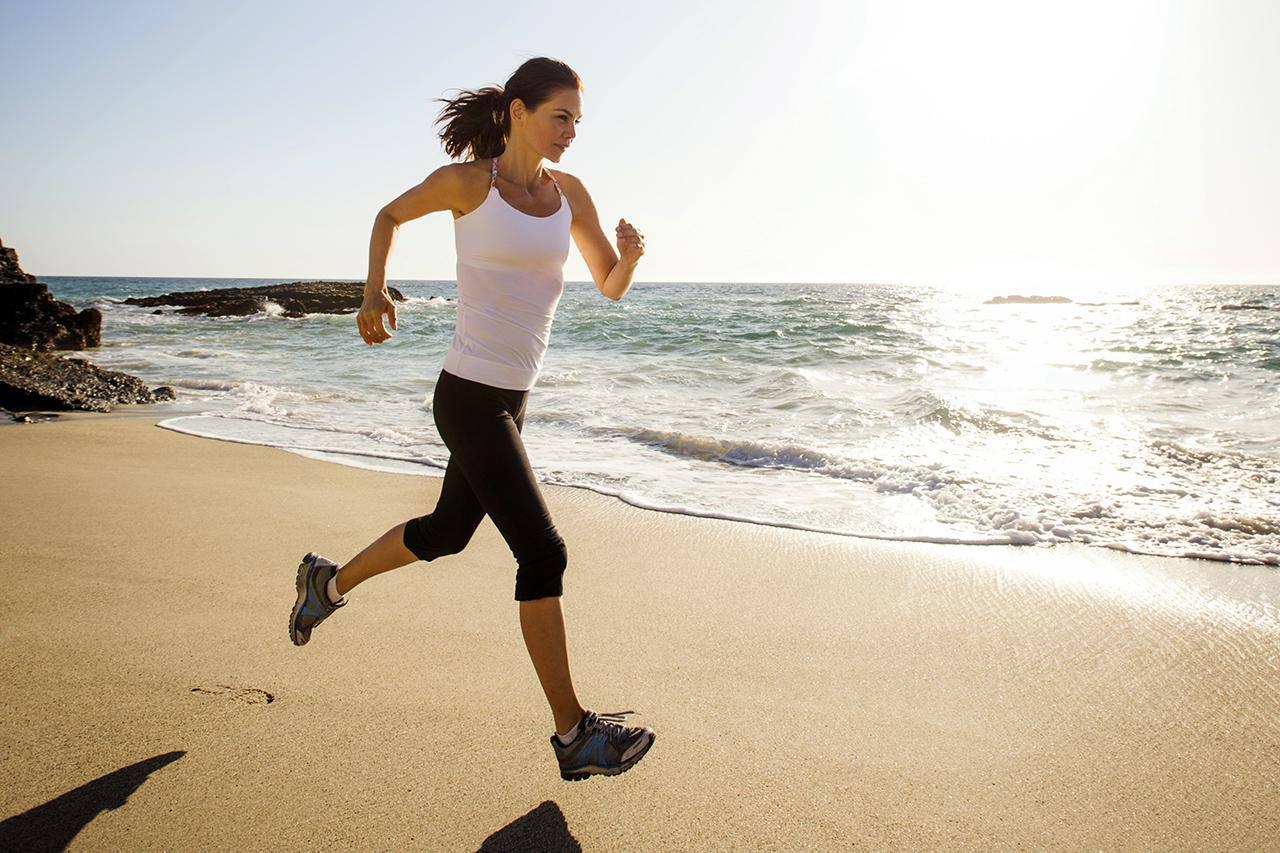 Mixed Race Woman Running On Beach